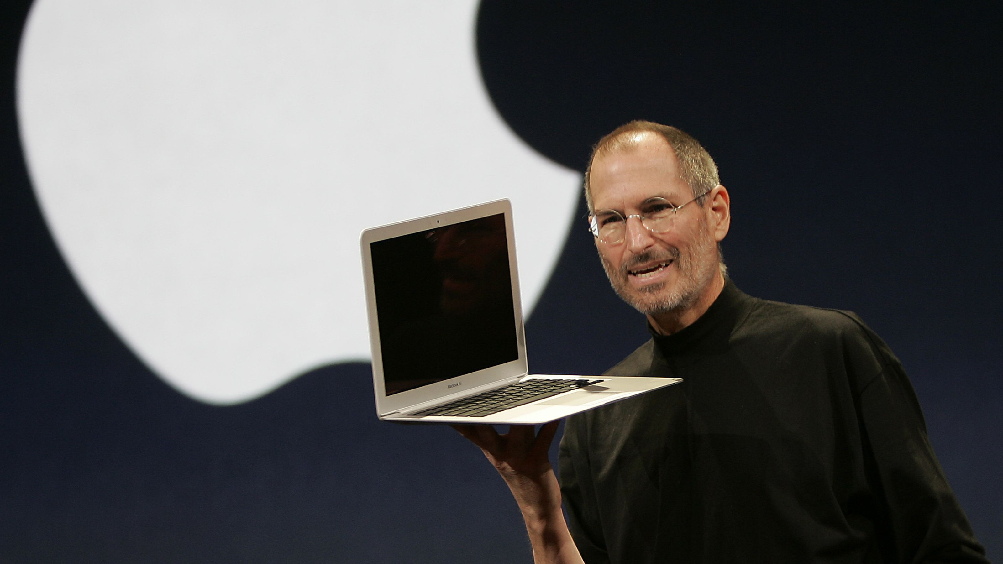 Steve Jobs holding a MacBook Air in one hand